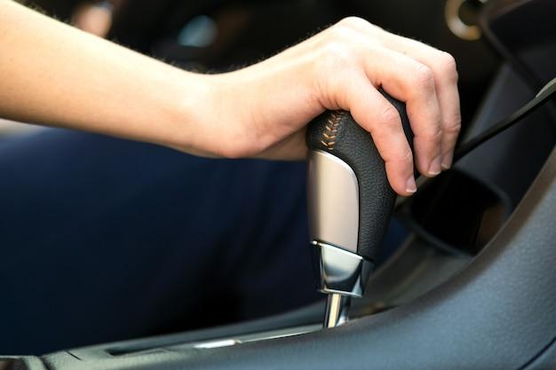 Perto de uma mulher motorista segurando a mão na alavanca de mudança automática, dirigindo como um carro