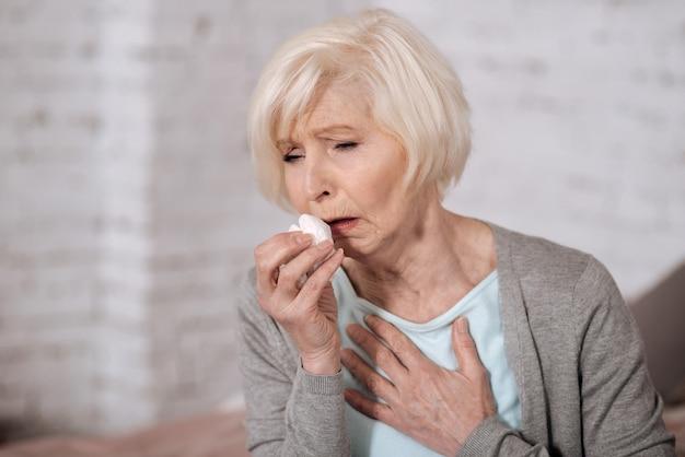 Perto de uma mulher muito idosa, segurando o guardanapo e tossindo muito.