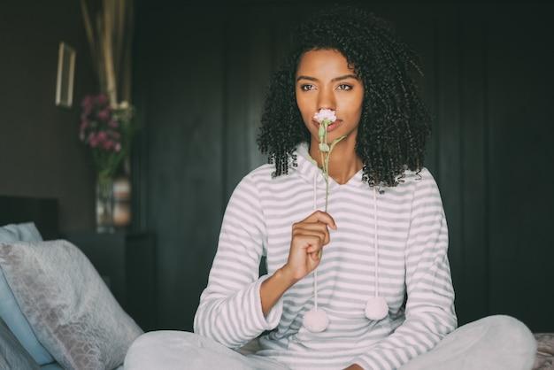 Perto de uma mulher negra bonita com cabelos cacheados, cheirando uma flor rosa, sente-se na cama, olhando para longe