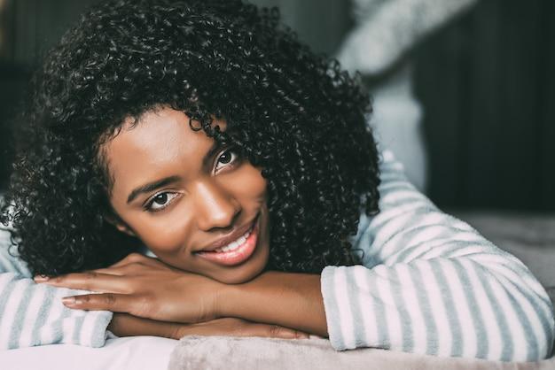 Perto de uma mulher negra com cabelos cacheados, sorrindo e deitada na cama, olhando para a câmera