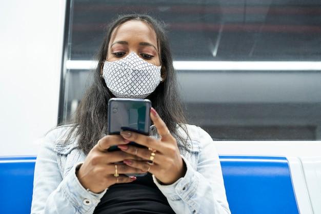 Perto de uma mulher negra sentada sozinha no vagão do metrô usando um smartphone.