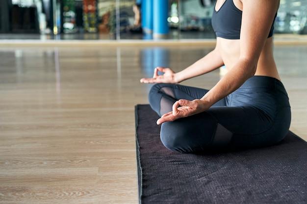Perto de uma mulher praticando ioga em uma academia, fazendo exercícios de meditação.