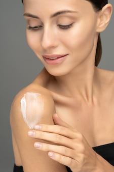 Perto de uma mulher sorridente, aplicando protetor solar ou loção hidratante cosmética