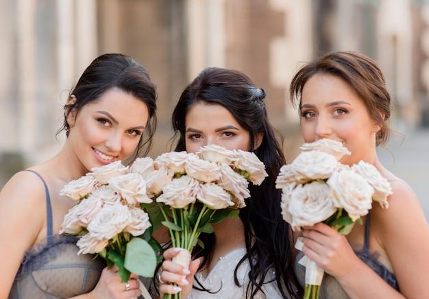 Perto de uma noiva morena junto com as damas de honra enterrando seus rostos atrás de buquês de casamento e olhando para a câmera