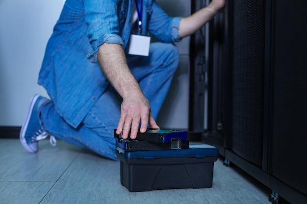 Perto de uma pequena caixa preta com instrumentos perto do engenheiro profissional enquanto trabalha