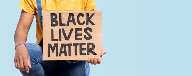 Perto de uma pessoa irreconhecível segurando uma faixa com o slogan black lives matter