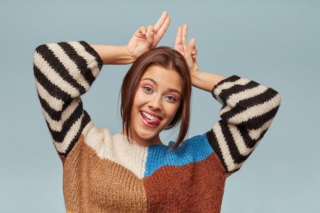 Perto de uma piada engraçada linda jovem, feliz, faz chifres na cabeça com os dedos