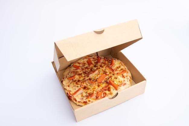 Perto de uma pizza em uma caixa de papelão contra fundo branco pizza delivery. menu de pizza.