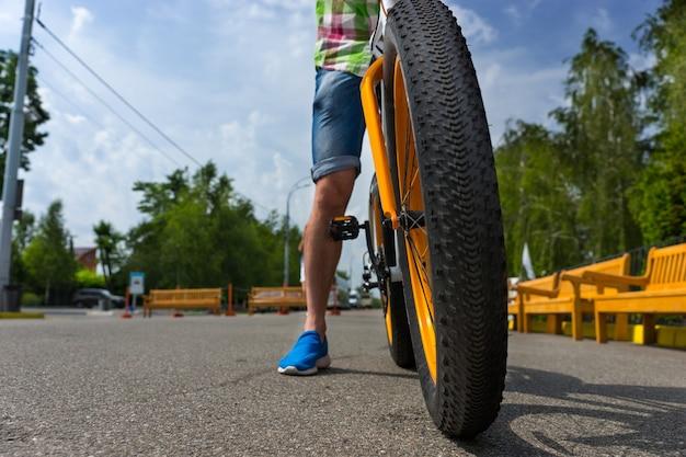 Perto de uma roda de bicicleta com um homem andando pelo parque