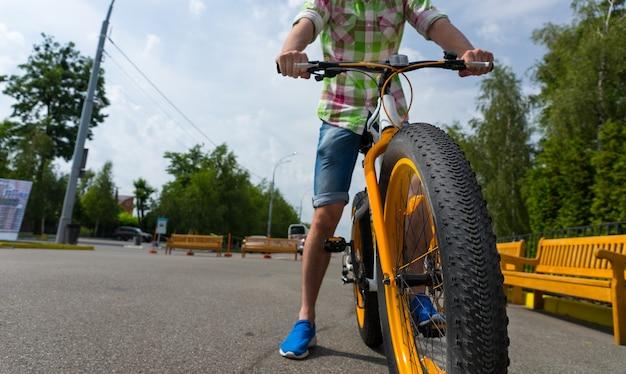 Perto de uma roda de bicicleta com um jovem andando pelo parque