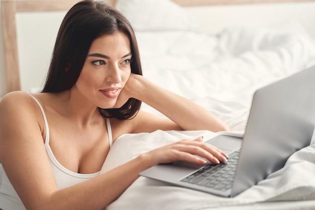 Perto de uma senhora bonita de cabelos escuros sentada com um gadget em seu quarto e digitando uma mensagem no teclado
