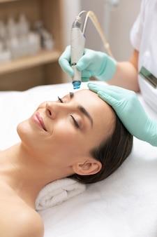 Perto de uma senhora calma e relaxada deitada com os olhos fechados e um cosmetologista profissional limpando sua pele com ferramenta de dermoabrasão