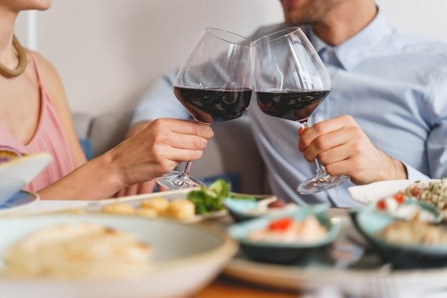 Perto de uma senhora e um cavalheiro tilintando copos de bebida alcoólica enquanto está sentado à mesa com comida no café