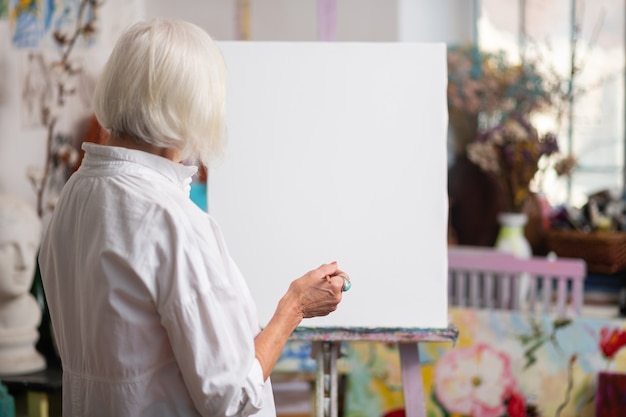 Perto de uma tela branca. mulher idosa de cabelos loiros em pé perto de uma tela branca antes de pintar
