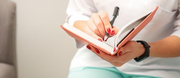 Perto de uma terapeuta médica escreve notas em um bloco de notas médico sentado em um consultório médico
