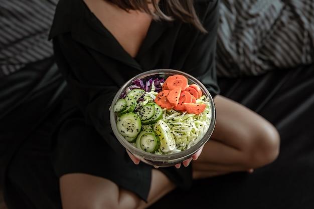 Perto de uma tigela grande com salada de legumes preparada na hora em mãos femininas.