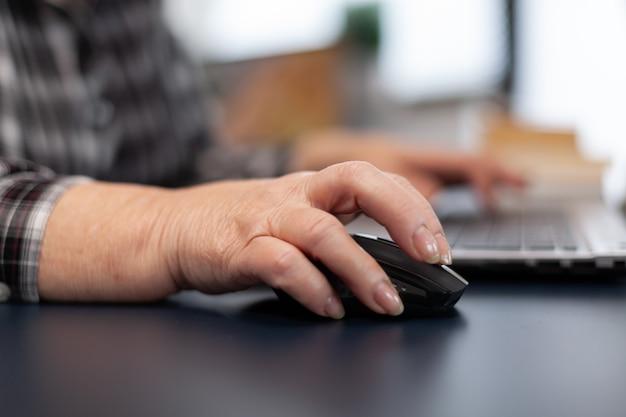 Perto de uma velha senhora empreendedora usando o mouse no escritório em casa
