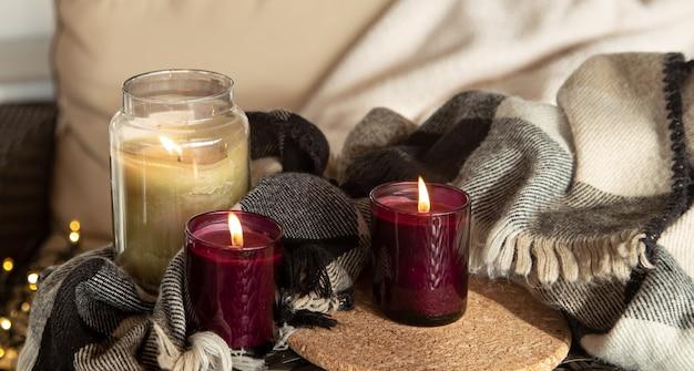 Perto de velas acesas em castiçais com detalhes do conforto do lar.