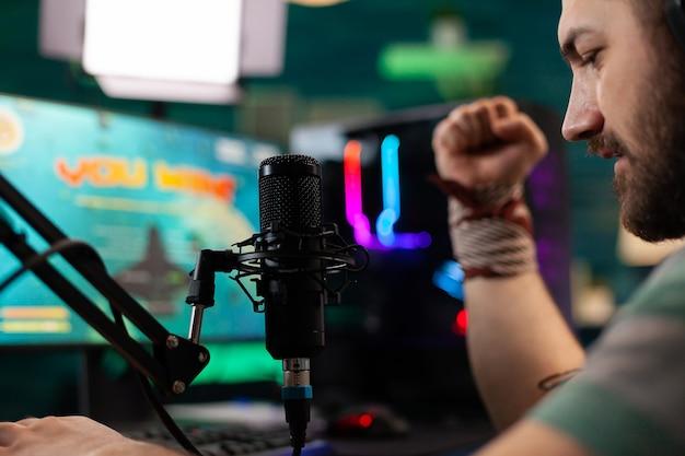 Perto de videogames de atirador vencedores de streamer para competição ao vivo em home studio. transmissão cibernética online durante torneios de jogos usando um pc poderoso com rgb.
