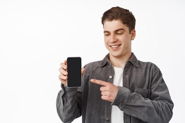 Perto do alegre cara caucasiano apontando o dedo para o smartphone, mostrando o aplicativo de tela do celular, aplicativo de interface, de pé em branco.