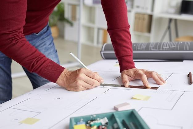 Perto do arquiteto irreconhecível, desenhando plantas enquanto se inclina sobre a mesa no local de trabalho,