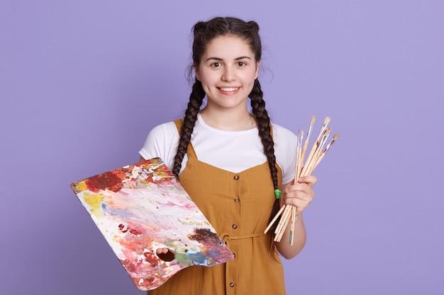 Perto do artista caucasiano jovem bonita com pincel e paleta de cores