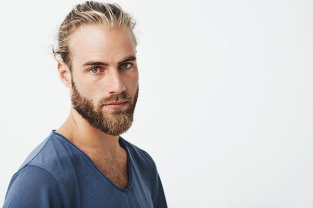 Perto do belo homem sueco com penteado elegante e barba na camiseta azul, olhando com expressão séria.