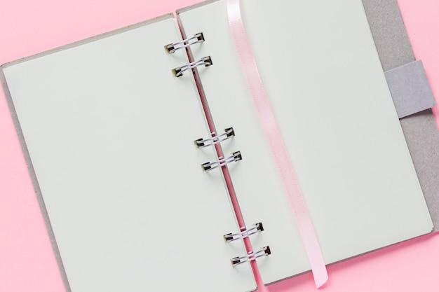 Perto do caderno vazio aberto com capa de papel reciclado em fundo colorido rosa pastel
