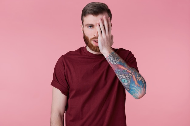 Perto do cansado e decepcionado jovem barbudo com a mão tatuada, cobre parte do rosto com a mão. isolado sobre o fundo rosa.