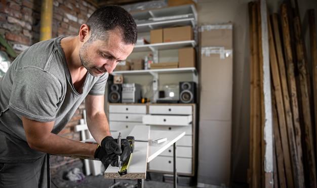 Perto do carpinteiro focado, segurando a régua e o lápis enquanto faz marcas na madeira na mesa da oficina.