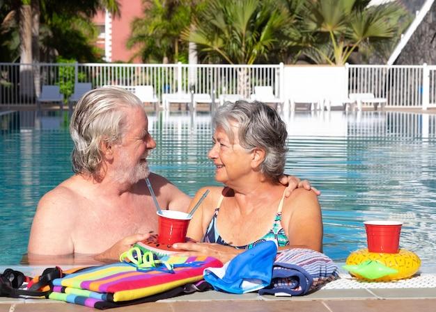 Perto do casal de idosos sorrindo e aproveitando o tempo livre na piscina. sol no rosto. estilo de vida feliz e saudável na aposentadoria