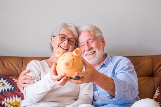 Perto do casal sênior, mostrando o cofrinho para economizar dinheiro. casal de idosos segurando o cofrinho para investimento e o conceito de planejamento futuro. casal feliz aposentado segurando o cofrinho juntos em casa