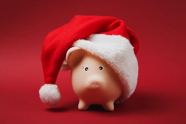 Perto do cofrinho rosa com chapéu de natal, isolado em fundo vermelho brilhante. acumulação de dinheiro, investimento, serviços bancários ou comerciais, conceito de riqueza. copie a simulação de publicidade do espaço.