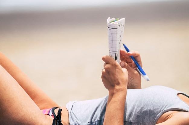 Perto do corpo da mulher de biquíni lendo e escrevendo estilo de vida na temporada de verão