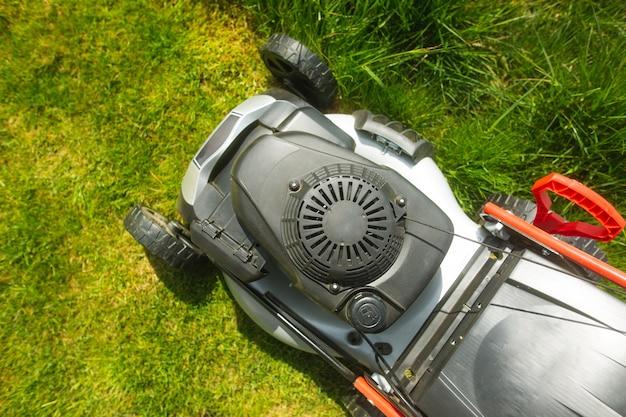 Perto do cortador de grama na grama, leia sobre como cortar a grama no jardim, conceito de jardinagem