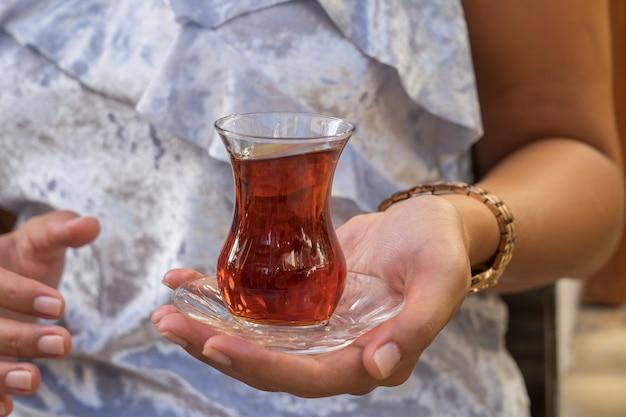 Perto do delicioso chá vermelho turco com o tradicional vidro em forma de pêra na mão da mulher, turquia