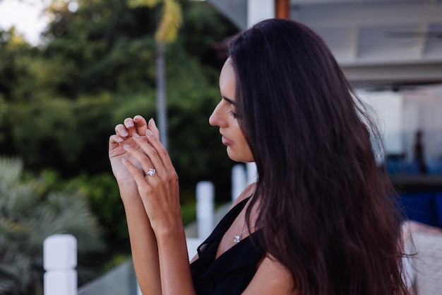 Perto do elegante anel de diamante no dedo da mulher. mulher de vestido preto. amor e conceito de casamento. luz natural suave e foco seletivo.