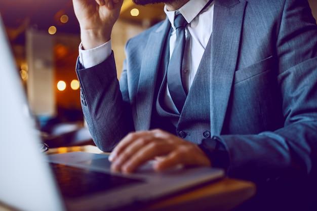Perto do elegante empresário de terno sentado no café e usando o laptop. as mãos estão no teclado. foco seletivo nas mãos.