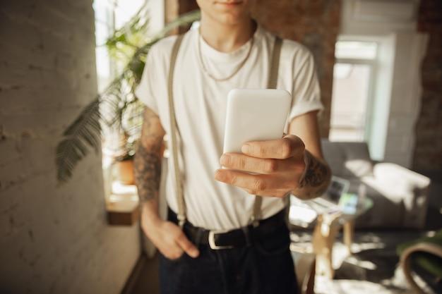 Perto do elegante homem caucasiano usando smartphone, tomando selfie. navegar, fazer compras online, navegar, apostar, trabalhar. conceito de educação, freelance, arte e negócios. beber café.