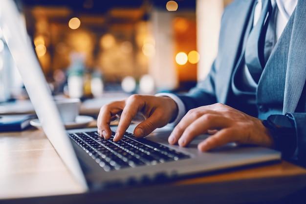 Perto do empresário caucasiano de terno sentado no café e digitando no relatório financeiro do laptop. as mãos estão no teclado.