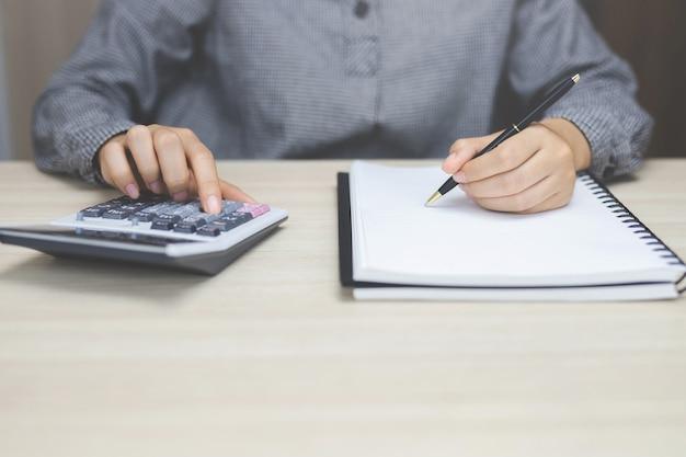 Perto do empresário ou contador mão segurando caneta trabalhando na calculadora para calcular dados de negócios, documento de contabilidade e computador portátil no escritório, conceito de negócio
