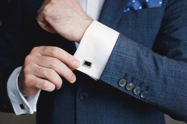 Perto do empresário usando botões de punho. homem de negócios de moda jovem elegante vestindo terno.