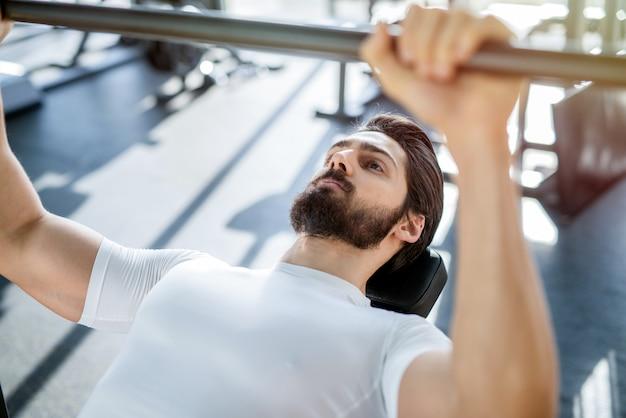 Perto do forte homem focado, treinando no ginásio, segurando a barra pesada no ginásio brilhante.