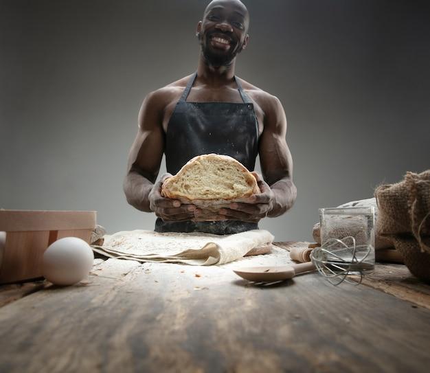 Perto do homem afro-americano cozinha cereais frescos, pão, farelo na mesa de madeira. comer saboroso, nutrição, produto artesanal. alimentos sem glúten, estilo de vida saudável, fabricação orgânica e segura. feito à mão.