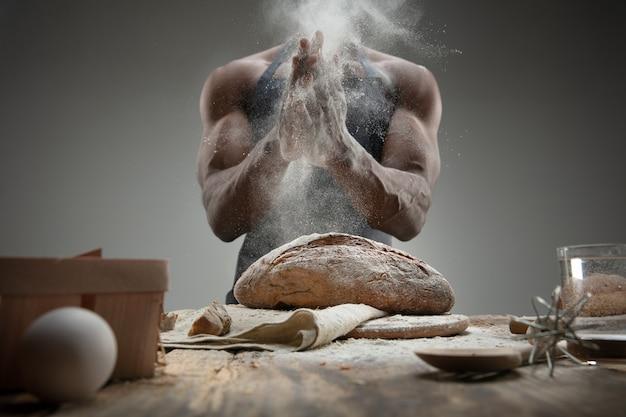 Perto do homem afro-americano cozinha cereal fresco, pão, farelo na mesa de madeira. comer saboroso, nutrição, produto artesanal. alimentos sem glúten, estilo de vida saudável, fabricação orgânica e segura. feito à mão.