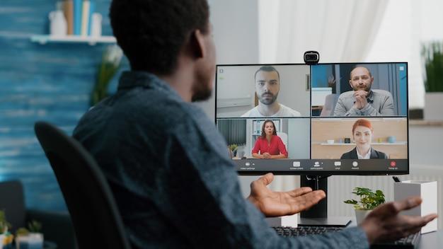 Perto do homem afro-americano na videoconferência online com seus colegas. usuário de computador trabalhando em casa, no escritório doméstico, conversando usando comunicação à distância pela internet