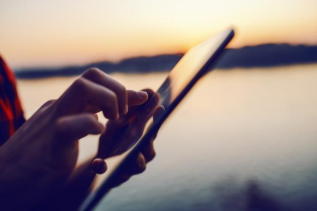 Perto do homem branco, usando o tablet na natureza ao pôr do sol junto ao rio.