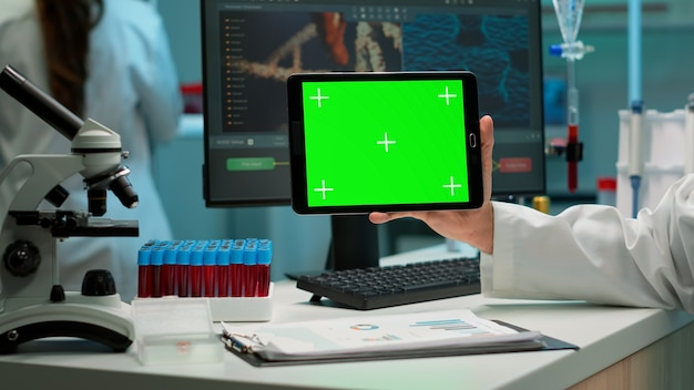 Perto do homem cientista segurando o tablet com maquete verde em laboratório equipado moderno. equipe de microbiologistas fazendo pesquisa de vacina, escrevendo no dispositivo com chroma key, display isolado.