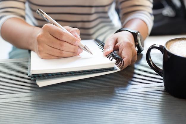 Perto do homem de negócios de pessoas casuais sentar, beber café, o bloco de notas e o freelancer trabalhando na mesa e no telefone móvel inteligente