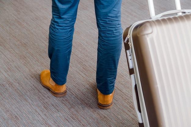 Perto do homem de negócios jovem com bagagem mala no tapete no aeroporto.